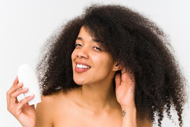 Jonge afrovrouw die een vochtinbrengende crème geïsoleerd het proberen aan het luisteren van een roddel houdt.