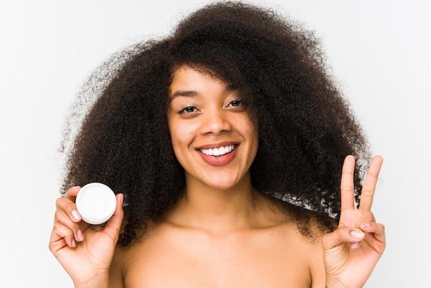 Jonge afrovrouw die een vochtinbrengende crème geïsoleerd houdt tonend nummer twee met vingers.