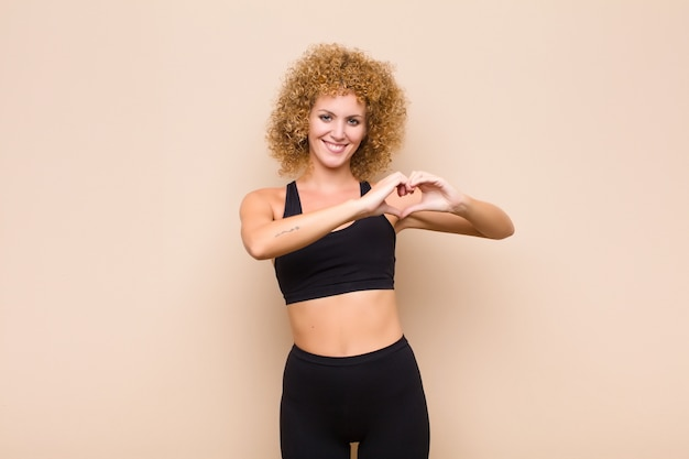 Jonge afrovrouw die en gelukkig, leuk, romantisch en in liefde glimlachen voelen, die hartvorm met het concept van de beide handsport maken