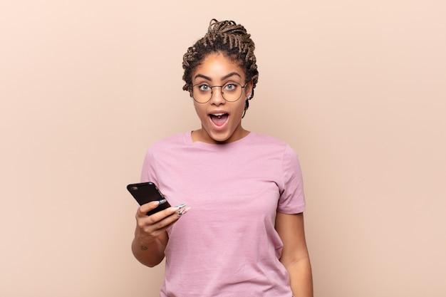 Jonge afrovrouw die geïsoleerd erg geschokt of verrast kijkt