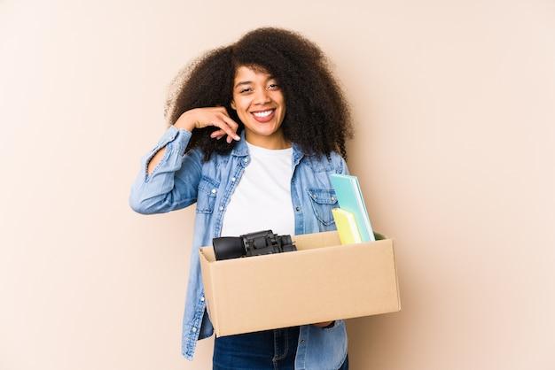 Jonge afrovrouw die geïsoleerd huis verhuist jonge afrovrouw die een gsm-gebaar met vingers toont.