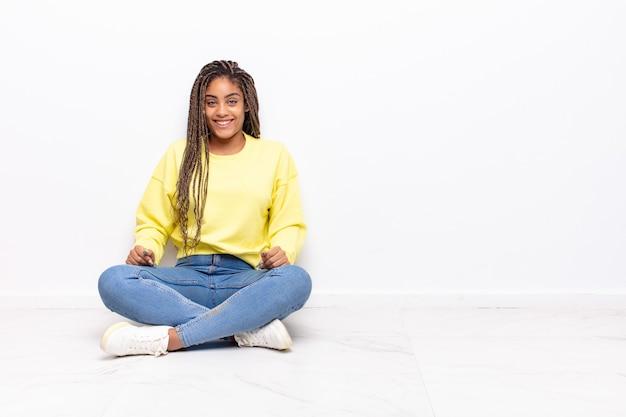 Jonge afrovrouw die gelukkig en maf met een brede, leuke, gekke geïsoleerde glimlach kijkt
