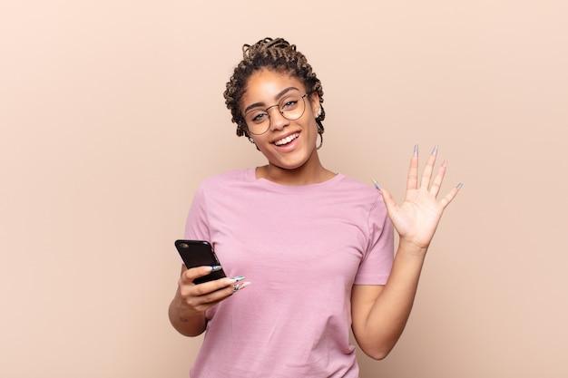 Jonge afrovrouw die gelukkig en opgewekt glimlacht, hand zwaait, u verwelkomt en begroet, of afscheid neemt. slimme telefoon concept