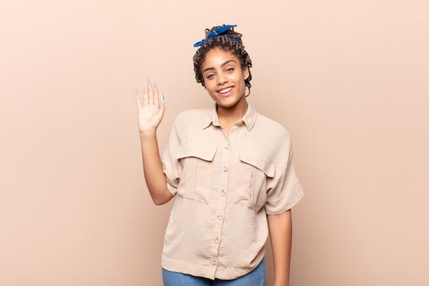 Jonge afrovrouw die gelukkig en opgewekt glimlacht, hand zwaait, u verwelkomt en begroet, of afscheid neemt