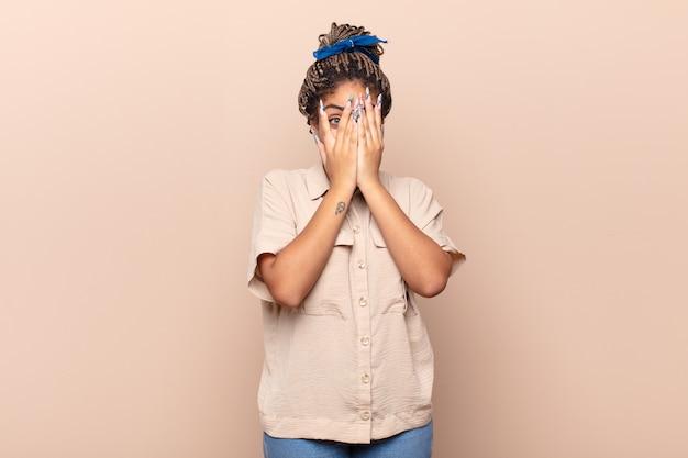 Jonge afrovrouw die gezicht bedekt met handen, tussen vingers gluurt met verbaasde uitdrukking en opzij kijkt
