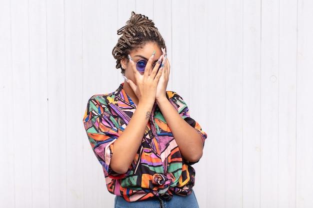 Jonge afrovrouw die gezicht behandelt met handen, die tussen vingers gluren