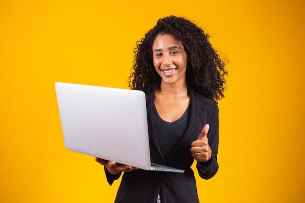 Jonge afrovrouw die laptop computer met behulp van