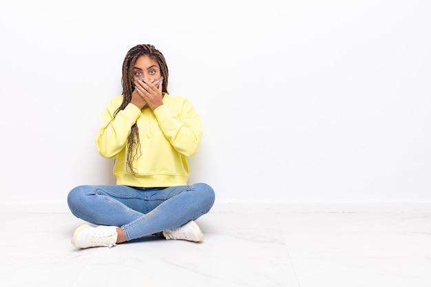 Jonge afrovrouw die mond behandelt met handen met een geschokte, verbaasde geïsoleerde uitdrukking