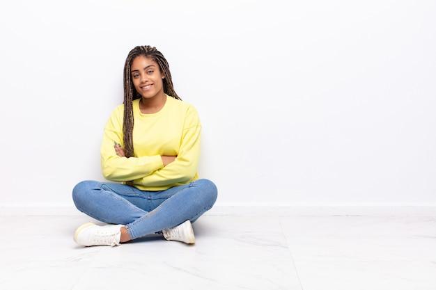 Jonge afrovrouw die naar camera glimlacht met gekruiste armen en een gelukkige, zelfverzekerde, tevreden uitdrukking, zijaanzicht