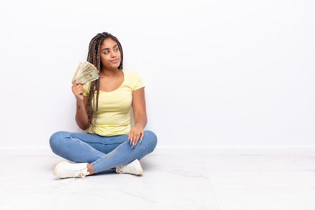 Jonge afrovrouw die op profielweergave ruimte vooruit wil kopiëren, denken, zich voorstellen of dagdromen