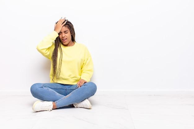 Jonge afrovrouw die palm opheft aan voorhoofd die oeps denken