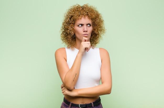 Jonge afrovrouw die, twijfelachtig en verward denkt, met verschillende opties denkt, zich afvraagt welke beslissing te nemen tegen groene muur