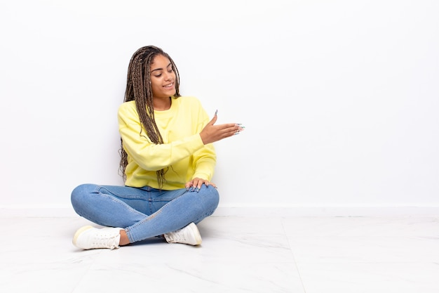 Jonge afrovrouw die u glimlacht, u begroet en een handschud aanbiedt om een succesvolle overeenkomst, samenwerkingsconcept te sluiten