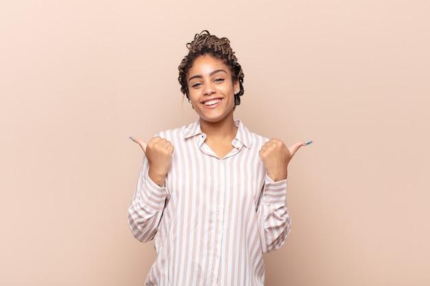 Jonge afrovrouw die vreugdevol glimlacht en er gelukkig uitziet, zich zorgeloos en positief voelt met beide duimen omhoog