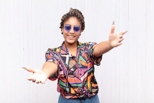 Jonge afrovrouw die vrolijk glimlacht en een warme, vriendelijke, liefdevolle welkomstomhelzing geeft, zich gelukkig en schattig voelt