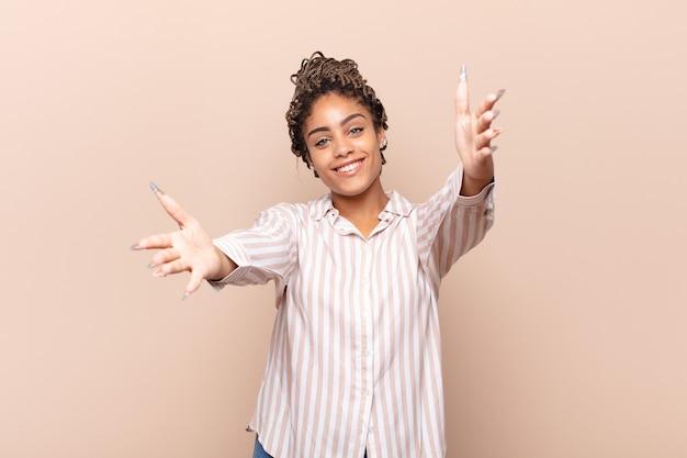 Jonge afrovrouw die vrolijk glimlacht en een warme, vriendelijke, liefdevolle welkomstomhelzing geeft