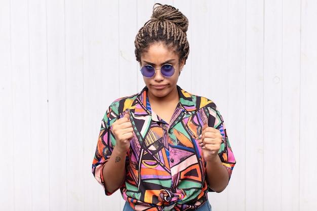 Jonge afrovrouw die zelfverzekerd, boos, sterk en agressief kijkt, met vuisten klaar om te vechten in bokspositie