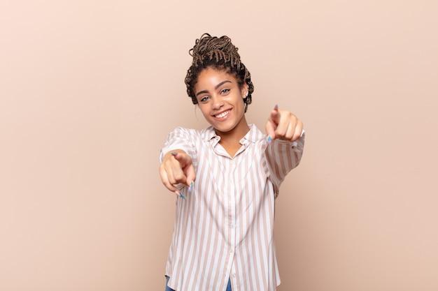 Jonge afrovrouw die zich gelukkig en zelfverzekerd voelt, met beide handen wijst en lacht