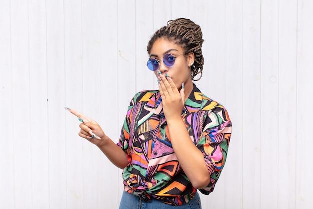 Jonge afrovrouw die zich gelukkig, geschokt en verrast voelt