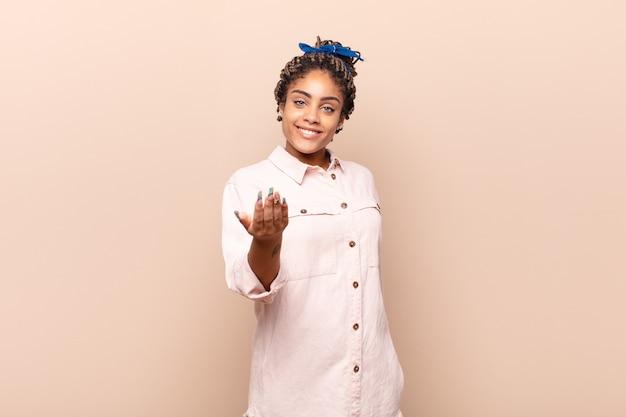Jonge afrovrouw die zich gelukkig, succesvol en zelfverzekerd geïsoleerd voelt