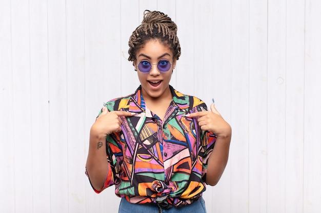 Jonge afrovrouw die zich gelukkig, verrast en trots voelt, wijzend naar zichzelf