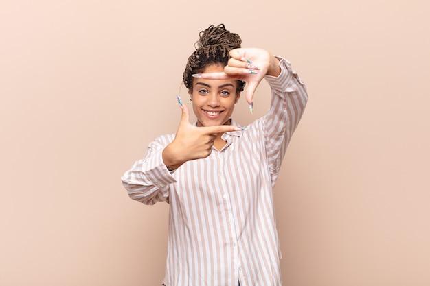 Jonge afrovrouw die zich gelukkig, vriendelijk en positief geïsoleerd voelt