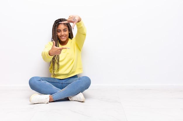Jonge afrovrouw die zich gelukkig, vriendelijk en positief voelt, glimlacht en een portret of fotolijst met handen maakt
