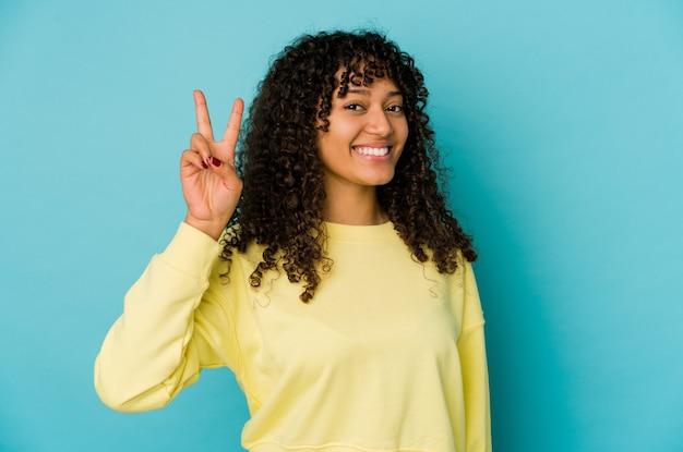 Jonge afrovrouw geïsoleerd blij en zorgeloos met een vredessymbool met vingers