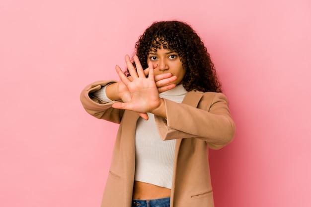 Jonge afrovrouw geïsoleerde status met uitgestrekte hand die stopbord toont, dat u verhindert
