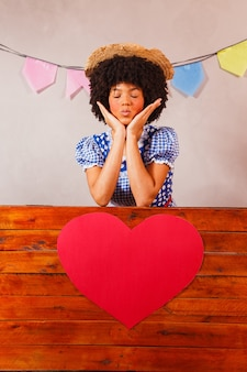 Jonge afrovrouw gekleed voor junina-feest achter een houten plank met een hart