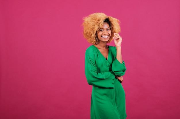Jonge afrovrouw in stijlvolle groene jurk die in de camera kijkt en glimlacht terwijl ze over een geïsoleerde achtergrond staat.
