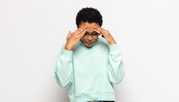 Jonge afrovrouw kijkt gestrest en gefrustreerd, werkt onder druk met hoofdpijn en heeft problemen