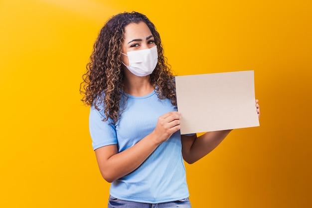Jonge afrovrouw met kaart met vrije ruimte voor tekst. promotieconcept. aanbod. zwarte vrijdag. nieuw normaal