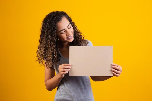 Jonge afrovrouw met kaart met vrije ruimte voor tekst. promotieconcept. aanbod. zwarte vrijdag