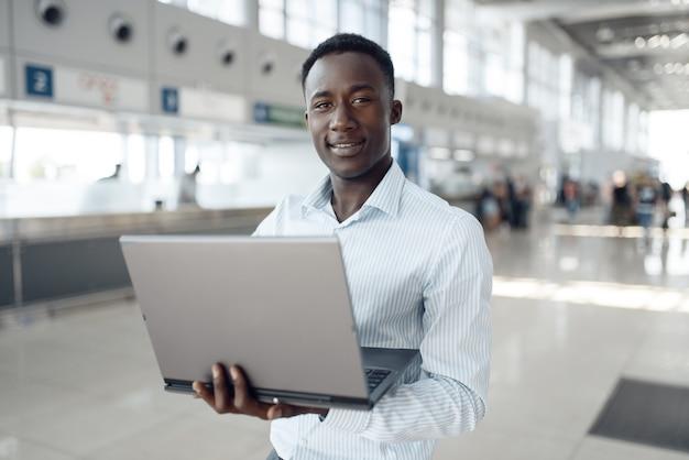 Jonge afrozakenman die aan laptop in autotoonzaal werkt. succesvolle zakenman op motorshow, zwarte man in formele kleding