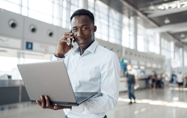 Jonge afrozakenman met laptop en telefoon in autotoonzaal. succesvolle zakenman op motorshow, zwarte man in formele kleding