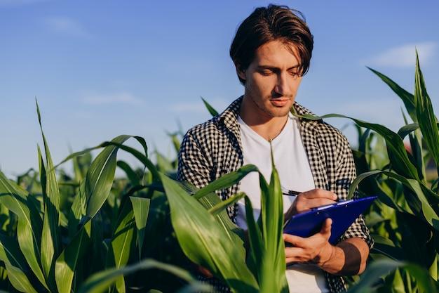 Jonge agronoom in een veld dat de opbrengst regelt en een aantekening maakt