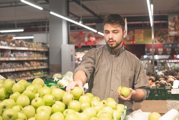 Jonge alleenstaande man groenten en fruit tonen bij het winkelen in de supermarkt supermarkt