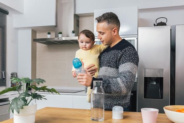 Jonge alleenstaande vader die een zuigfles klaarmaakt terwijl hij zijn baby thuis in de armen houdt