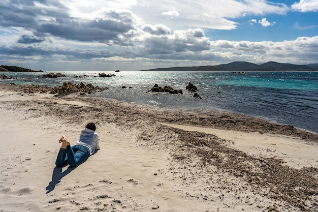 Jonge alleenstaande vrouw kijkt naar geweldige bewolkte hemel liggend op het strandzand in het herfst- of winterseizoen en denkt na over het toekomstige lot. eenzaam meisje in contact met de natuur om zichzelf te ontdekken