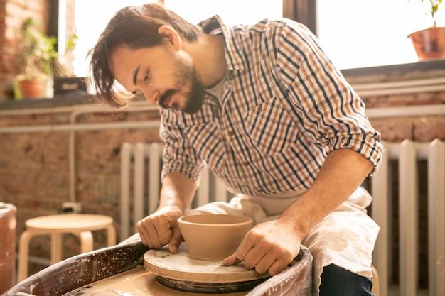 Jonge ambachtsman die over een roterend aardewerkwiel buigt terwijl hij speciaal draad gebruikt om een nieuw item van de apparatuur af te snijden