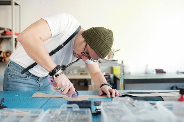 Jonge ambachtsman in vrijetijdskleding en muts die over tafel buigt tijdens het snijden van een stuk beige suède of leer in de werkplaats