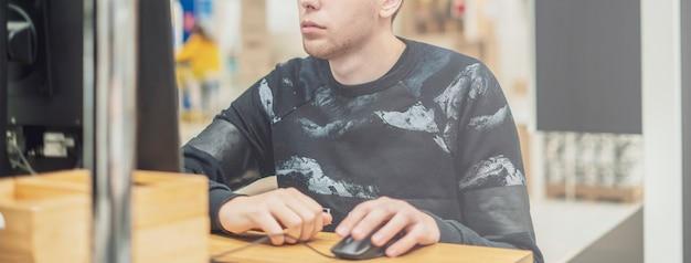 Jonge ambitieuze man in casual werken op een computer op kantoor