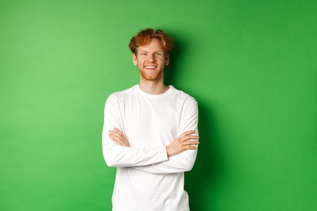 Jonge ambitieuze man met rood haar permanent over groene achtergrond, hand in hand gekruist op de borst en lachend.