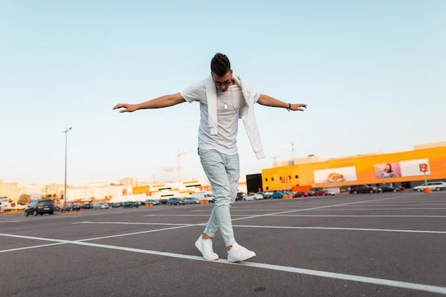 Jonge amerikaanse man houdt zijn evenwicht en loopt langs een witte lijn over het asfalt. aantrekkelijke man in een stijlvol t-shirt in zonnebril in trendy sneakers in vintage spijkerbroek is ontspant in de stad.