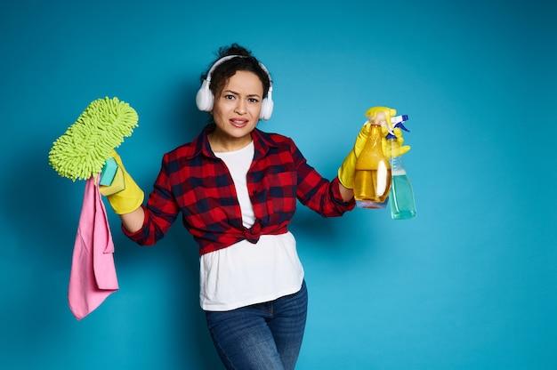 Jonge amerikaanse vrouw poseren voor de camera met schoonmaakmiddelen, verbijsterd voor haar aanstaande huiswerk