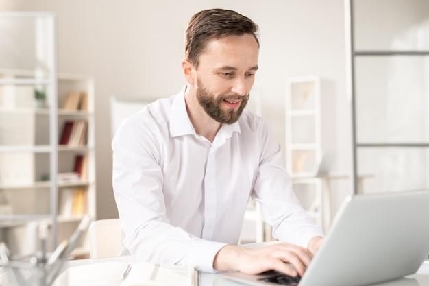 Jonge analist in wit overhemd typen op laptop toetsenbord terwijl netering informatie of browsen in het net