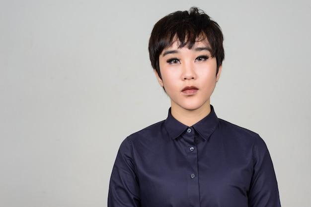 Jonge androgyne aziatische transgender vrouw tegen witte muur