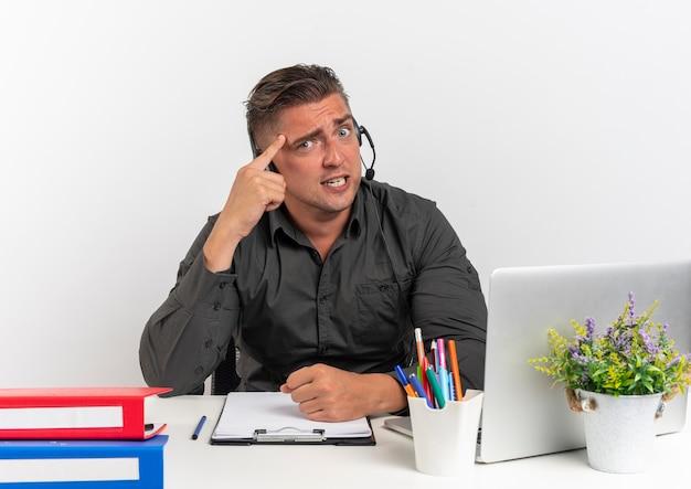Jonge angstig blonde kantoor werknemer man op koptelefoon zit aan bureau met office-hulpprogramma's met behulp van laptop legt vinger op hoofd kijken naar camera geïsoleerd op een witte achtergrond met kopie ruimte