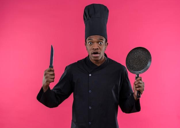 Jonge angstige afro-amerikaanse kok in uniform chef houdt mes en koekenpan geïsoleerd op roze achtergrond met kopie ruimte